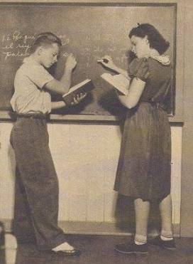 JUDY GARLAND AND MICKEY ROONEY DO THEIR LESSON They are seen working on their French assignment at the M-G-M studio school. Here, as at other studios, a school offering studies from primary grades through high school is maintained. For California state law requires that every screen actor of school age shall devote four hours daily to study.