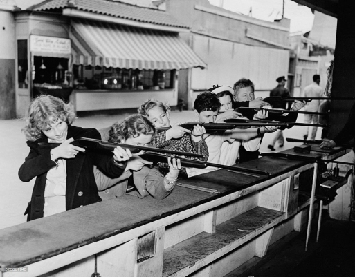 Suzanne, Betty Jaynes, John Arlington, Freddie Bartholomew, Judy Garland and Mickey Rooney try their luck at the rifle range, 1937