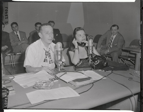 (Original Caption) Motion picture star Judy Garland answers the phone here, while on a visit to disc jockey Jack Eigen, (L). She took part in the radio program, during her stay in New York City.