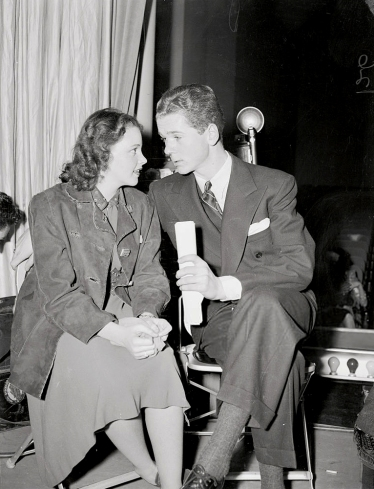 (Original Caption) Judy Garland and Jackie Cooper take a little time out during rehearsal of the American Calling program here. It was a broadcast coast to coast the following day, in celebration of the 147th Anniversary of the Ratification of the American Bill of Rights.