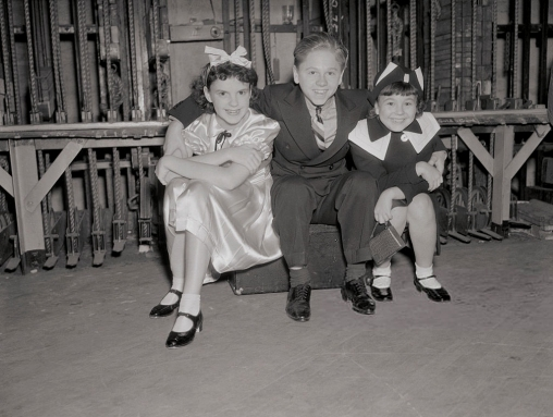(Original Caption) Seated under the grid of a Hollywood Theater are probably the greatest trio of up and coming juvenile stars in Hollywood. Left to right are Judy Garland, Mickey Rooney, and Jane Withers. The first is the protege of Louis B. Mayer, noted movie executive, who signed her for seven years. Mickey is the famous puck of midsummer night's dream and Jane Withers is the chief rival of Shirley Temple.
